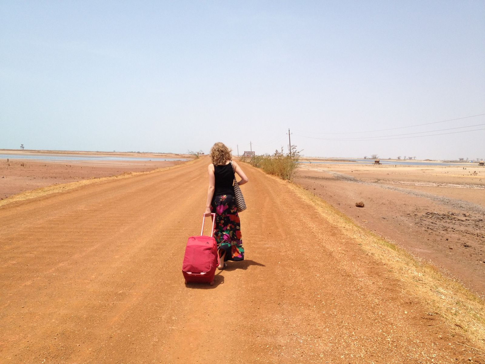 Girl dragging luggage on dusty road in Senegal, Africa.