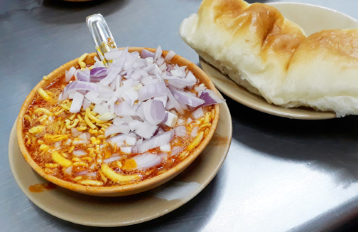 A bowl of misal and bread from Mumbai (sprouts in gravy)