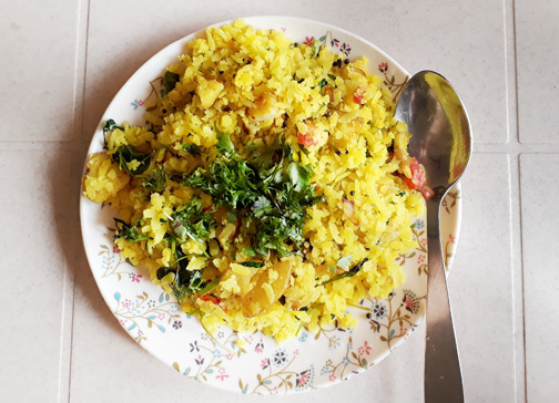 A plate of poha, a Marathi breakfast dish made of flattened rice and spices, in Mumbai