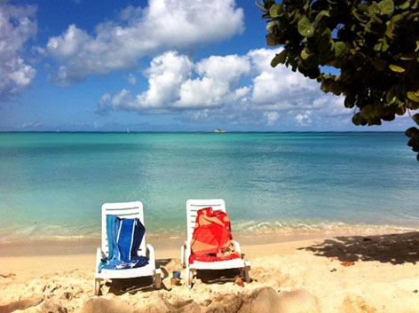 Two beach chairs, sand, and the turquoise Caribbean on the beach in Antigua