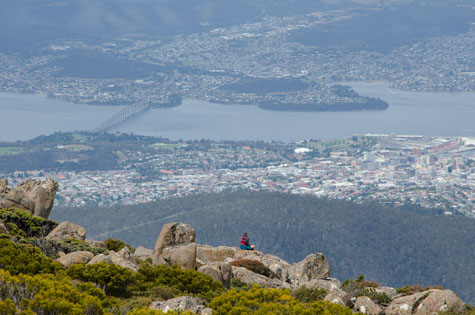 A hiker sits at the top of a mountain overlooking Hobart, Tasmania, after a hike