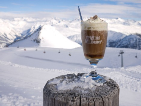 Schumli pflumli, a traditional plum schnapps and coffee drink in the Swiss Alps pictured before a snowy mountain