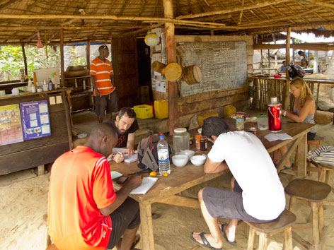Guests at communal kitchen table at Tribewanted, Sierra Leone