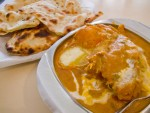 Butter chicken and a plate of naan, traditional mughlai food in Agra, India.